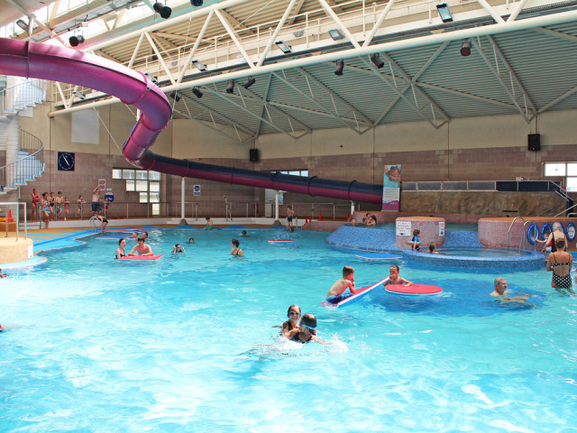 A busy swimming pool with children sitting on big floats