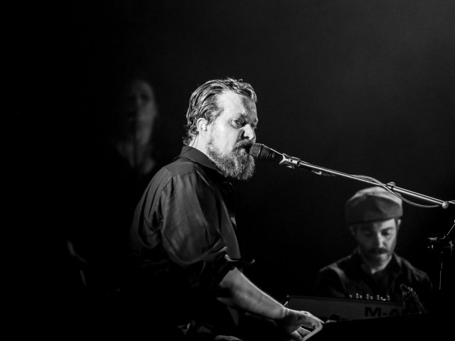 Black and white head shot of bearded man playing piano and singing into microphone