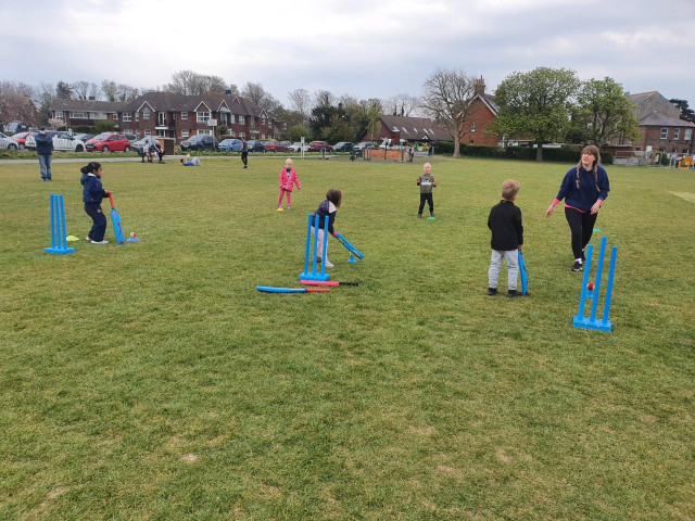 Small children and an instuctor on grass playing cricket with soft bats and wickets