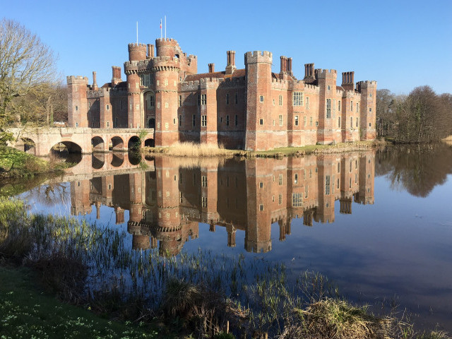 Herstmonceux castle and it's reflection in still moat water