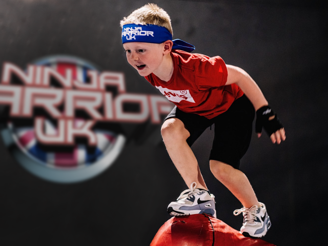 A little boy with a blue ninja warrior uk headband about to jump into a ball pit.