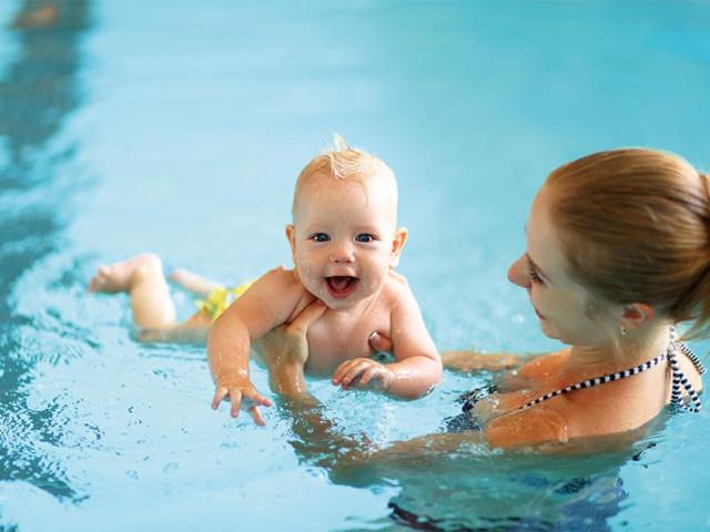 Mum holding baby in swimming pool