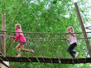 Kids running across the rope bridge at Groombridge Place
