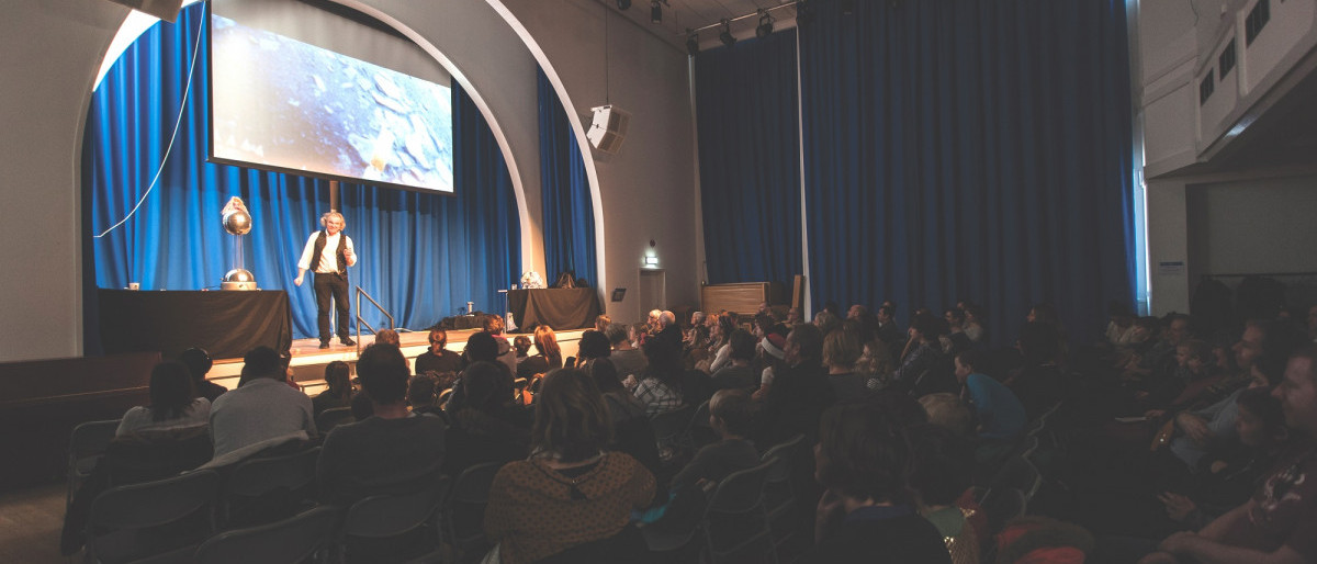 A man presenting a science show on stage with a theatre audience