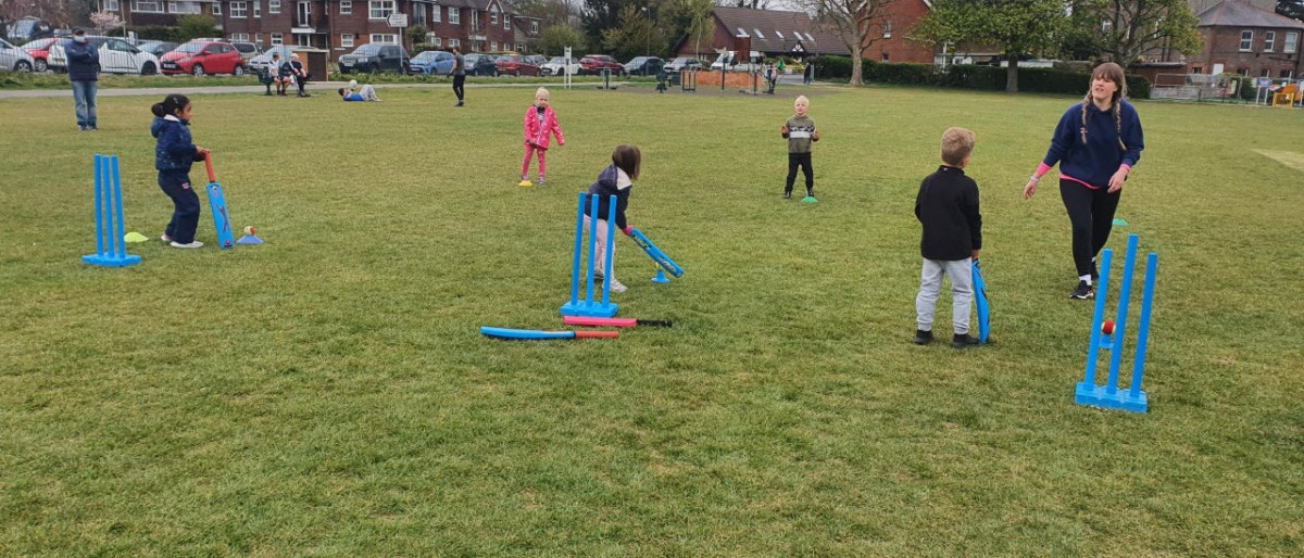 Small children and an instructor on grass playing cricket with soft bats and wickets