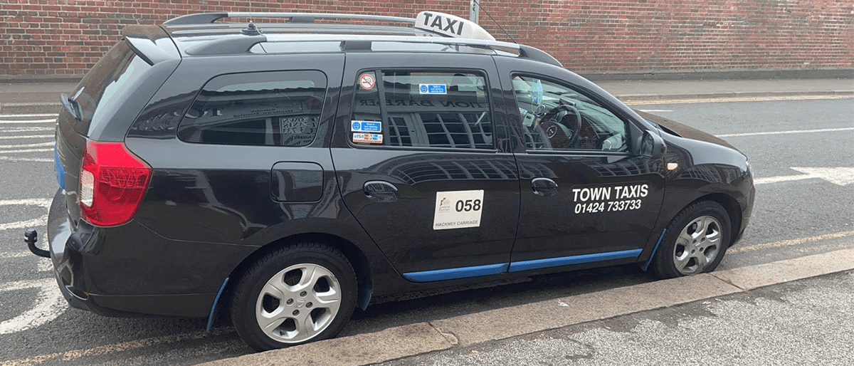 Black taxi with white words saying Town Taxis