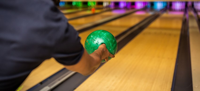 A person throwing a ball down the bowling alley